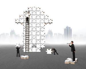 Businessman commanding workers to build arrow jigsaw puzzle with