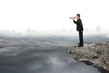 Businessman using megaphone yelling on cliff with gray cloudy ci