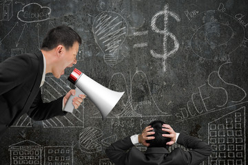 Boss using megaphone yelling at his employee with doodles wall