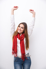 Smiling woman with raised hands up over gray background