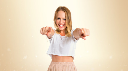 Blonde woman pointing to the front over white background