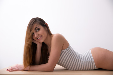 Happy young woman in bodysuit lying on the table