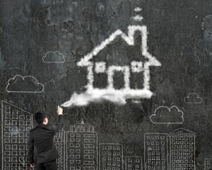 Businessman spraying house shape cloud paint with cityscape dood