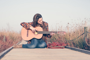 Woman playing guitar on a catwalk in the field enjoying nature