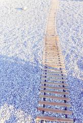 Wooden walkway on beach of pebbles