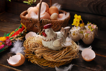 easter decoration of hen in the nest and wicker basket with eggs