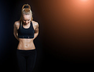 Athletic young woman showing trained body and pumped abdominals