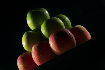 Apples red and green with low key lighting.