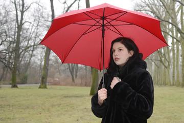 Deutschland, Berlin, traurige junge Frau mit Schirm im Park