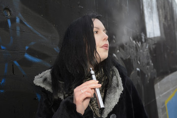 Junge Frau mit E-Zigarette, Berlin, Deutschland