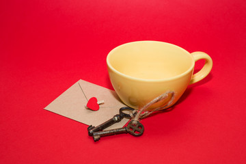 Envelope with heart, two keys and yellow cup on a red background