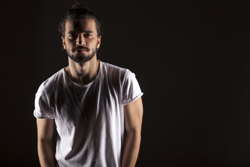 handsome young man with a beard on dark background