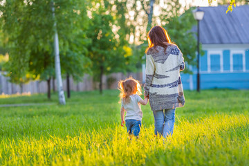 Mother and little daughter walking in sunny park