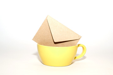 Envelope  in the yellow cup on a white background.