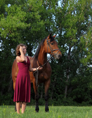 Attractive and shapely redhead woman with horse