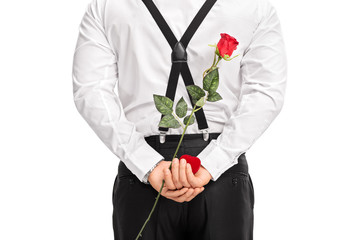 Man holding flower and a red box behind his back