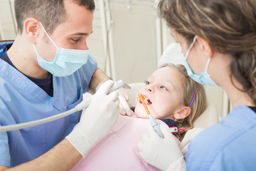 Dentist and dental assistant examining young girl teeth