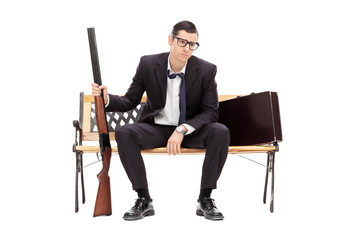 Upset businessman holding a rifle seated on a bench