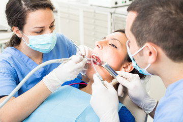 Dentist and dental assistant examining patient teeth