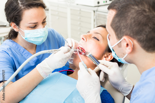 Dentist and dental assistant examining patient teeth - 78691737