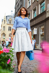 Woman in white skirt and blue blose.