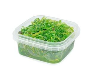 A plastic tub of fresh wakame seaweed on a white background