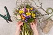 hands of florist making bouquet spring flowers - 78693169