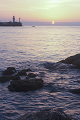 Sunrise over the sea with the lighthouse in the background