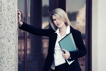 Happy young business woman with a folder at office building