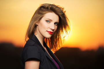 Portrait of young fashion woman at sunset