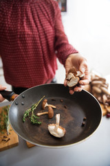 Closeup on young housewife cooking mushrooms in kitchen