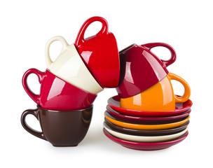 Stack of colorful mugs and saucers on white background