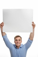 Young smiling man holding white empty paper.