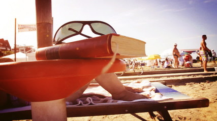 book and sun glasses at the beach