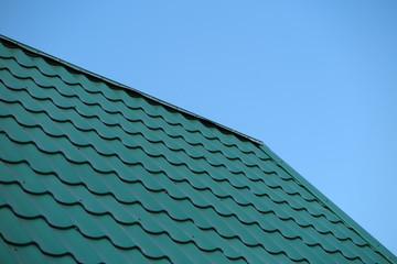 Modern metal tile roofing against a blue sky