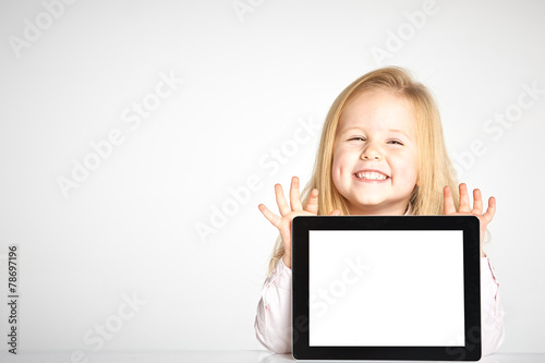 Leinwandbild Motiv Cute little and smiling girl plays with a tablet