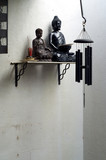two buddhas on shelf with incense and wind chime poster