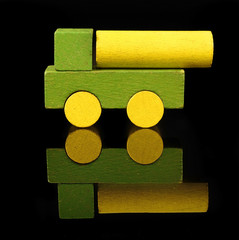 Tank truck of wooden blocks, traditional toy on black background