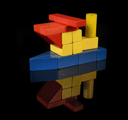 Tugboat of wooden blocks, traditional toy on black background