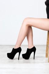 Closeup image of female legs in black heels