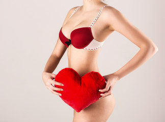 Closeup image of a sexy woman holding red heart