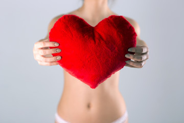 Closeup image of female hands holding red heart