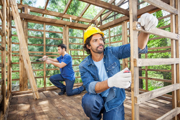 Construction Workers Working In Wooden Cabin