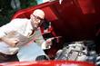 Mann mit roter Motorhaube Öl messen