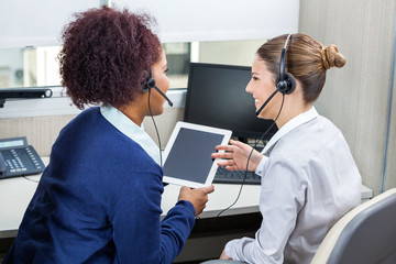 Smiling Call Center Employees Discussing While Using Digital Tab