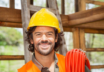 Happy Male Worker With Pipe At Construction Site