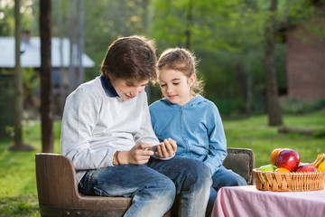 Siblings Using Smartphone At Campsite