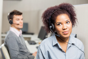 Female Customer Service Representative Wearing Headset In Office
