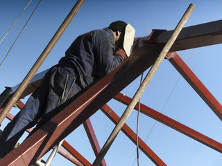 Welder with protective helmet welding metal on construction site