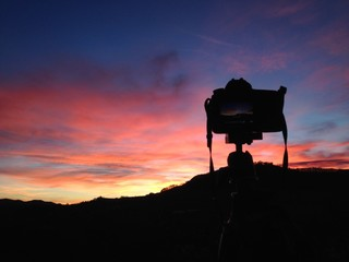 silhouetted camera in sunset sky